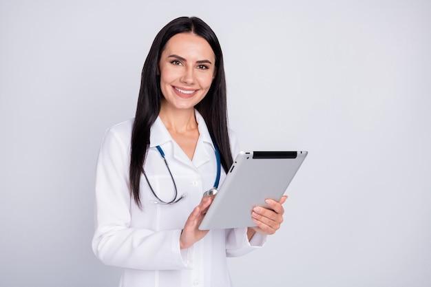 タブレットを保持している白い白衣の聴診器を持つプロの医師の女性