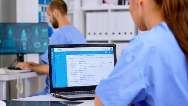 전문 의사 조수는 엑스레이와 의료 장비가 있는 노트북에서 의료 기록을 확인합니다. 병원 진료소에서 근무하는 의사가 예약을 하고 환자 등록을 분석합니다.