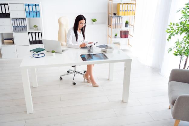 Профессиональная девушка-врач сидит в офисе медицинского центра и смотрит в планшет