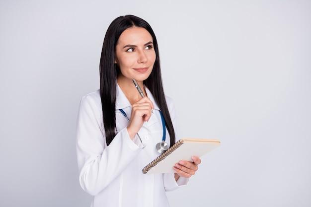 プロの医者の女の子がコピーブックに処方箋を書く空のスペースを考えて見える