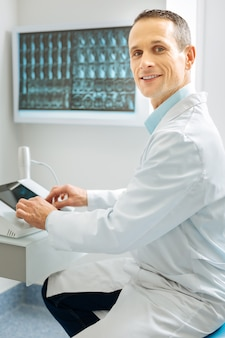 Professional doctor. nice professional male radiologist sitting near the x ray control panel and smiling while doing his job