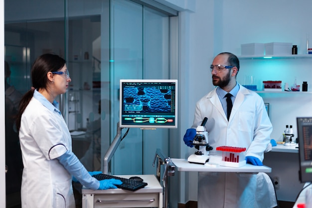 Dna 이미지 스캔을 분석하는 컴퓨터를 보고 있는 전문 의사 과학자
