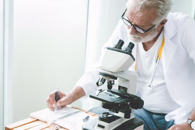 病院の実験室で専門の医師の科学者が新しいワクチンとウイルスを研究し、ノートのレポートを書きます。
