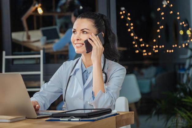 専門医。彼女のラップトップを使用し、彼女のオフィスで働いている間電話で話しているスマートな美しいポジティブな女性