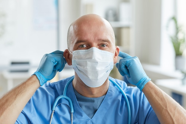 Professional doctor wearing blue uniform and latex gloves putting on protective mask on his face