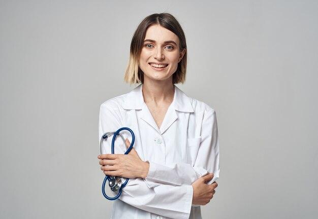 青い聴診器と白い医療用ガウンを持つプロの医師の女性