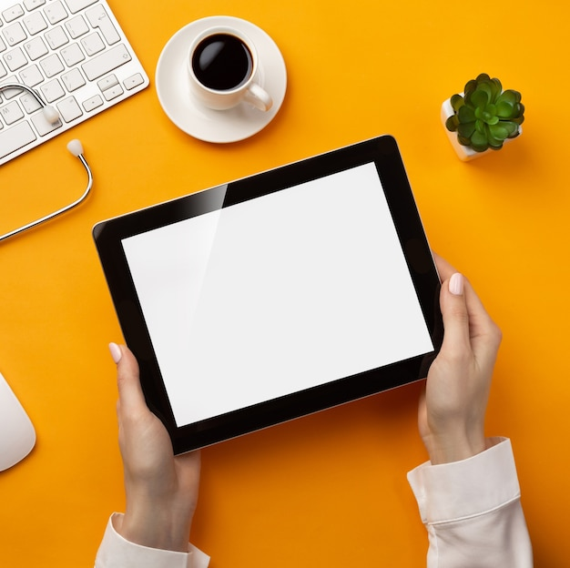Professional doctor writing medical records in a digital tablet with stethoscope, keyboard, coffee cup and mouse. top view with place for your text.
