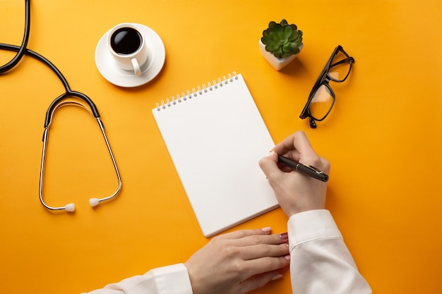 Professional doctor writing medical records in a notebook with stethoscope, coffee cup and glasses. top view with place for your text.