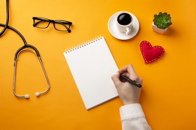 Professional doctor writing medical records in a notebook with stethoscope, coffee cup and heart