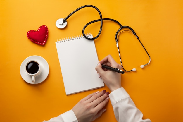 Professional doctor writing medical records in a notebook with stethoscope, coffee cup, syringe and heart