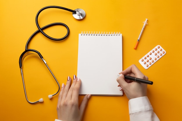 Professional doctor writing medical records in a notebook with stethoscope, syringe and pills. top view with place for your text.