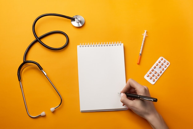 Professional doctor writing medical records in a notebook with stethoscope, syringe and pills