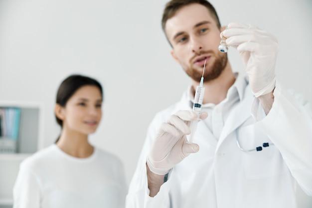 주사기에 액체를 가진 전문 의사