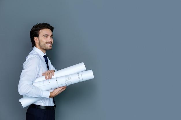 プロの図面。オフィスで働いている間笑顔で青写真を保持しているうれしそうな前向きな賢い人