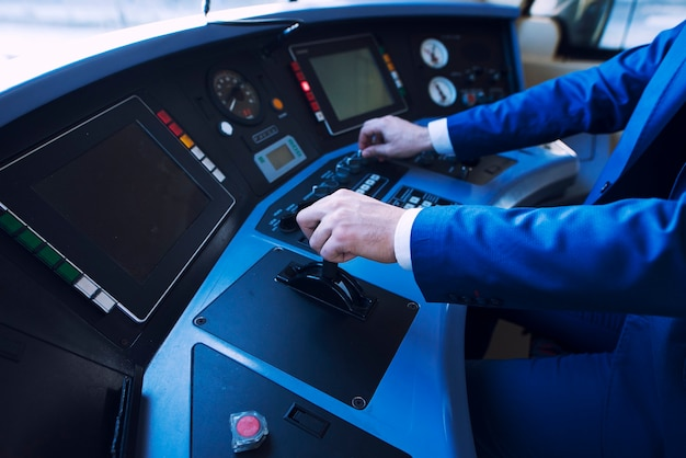 Professional driver in uniform operating in train cockpit and driving high speed train