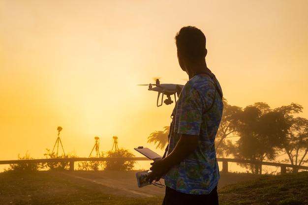 ドローンで遊ぶプロのドローンパイロットまたはストックフォトグラファー。夕焼け空を背景にシルエット