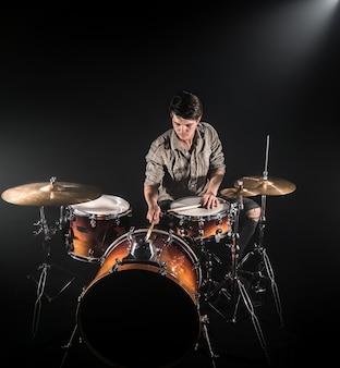 ドラムスティックとビンテージの外観と黒の背景のステージのドラムセットで演奏するプロのドラマー。上面図。煙の効果