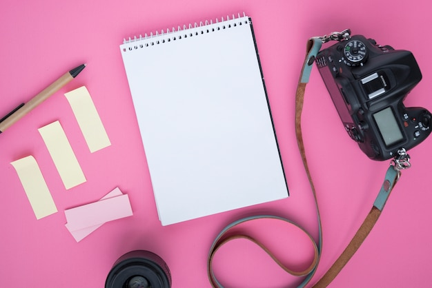Professional dslr digital camera; blank spiral notepad; sticky notes; pen; camera lens and belt on pink background