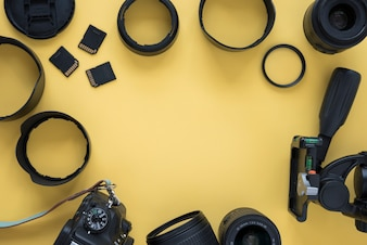 Professional dslr modern camera with camera accessories over yellow background