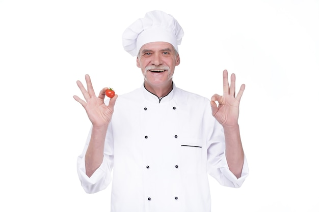 Professional elderly chef in white uniform and hat, holding tomato while staying on white wall