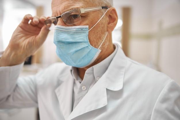그의 안경을 만지고 직장에서 심각한 찾고 전문 노인 건강 관리 노동자