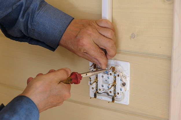 Professional electrical engineer performs installation of electrical sockets and wiring in a new wooden house