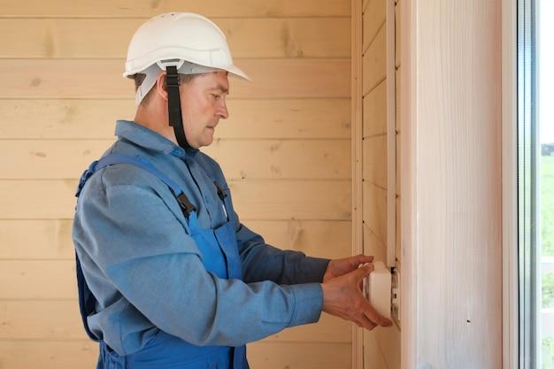 전문 전기 엔지니어가 새 목조 주택에 전기 소켓 및 배선 설치를 수행합니다.