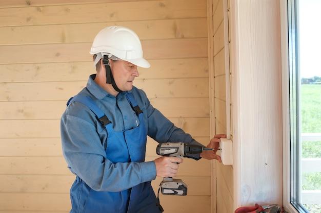 Профессиональный инженер-электрик выполняет установку электрических розеток и электромонтажа в новом деревянном доме.
