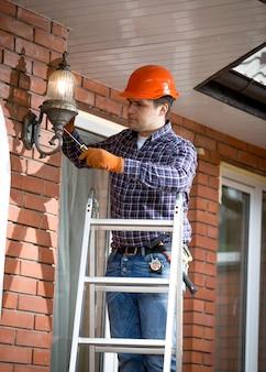 Профессиональный электрик, стоящий на лестнице и меняющий уличный светильник