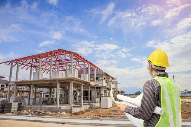 住宅建設現場の背景で保護ヘルメットと青写真の紙を持つプロのエンジニア建築家労働者