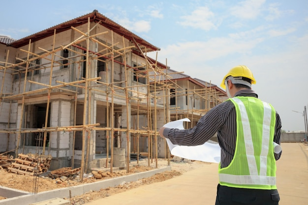 住宅建築建設現場の背景で保護ヘルメットと青写真紙を持つプロのエンジニア建築家労働者