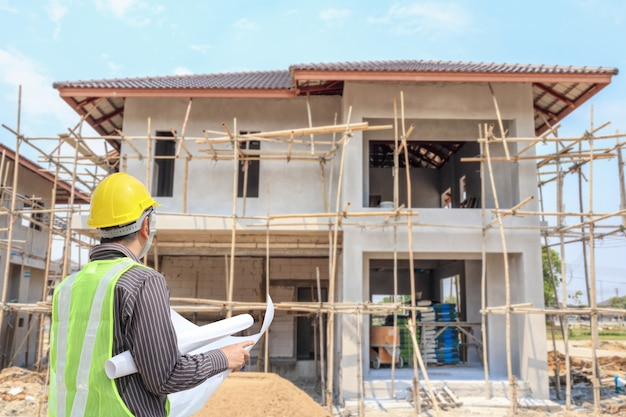 Professional engineer architect worker with protective helmet and blueprints paper at house building construction site background