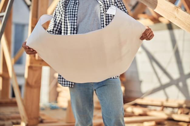 建築計画と紙を保持しているプロのエンジニア