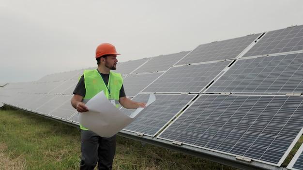 태양광 발전소 종이 계획의 설계를 배우는 전문 엔지니어는 생태학적 태양광 발전소 건설을 걷습니다. 지속 가능한 에너지. 녹색 에너지의 개념입니다.
