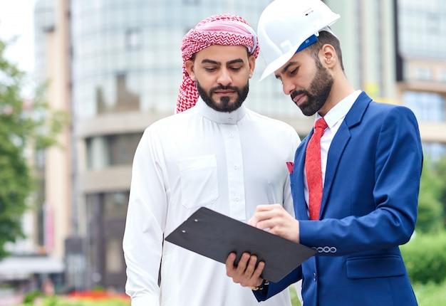 ビジネスセンターの前に屋外のアラブのクライアントと書類に署名するプロのエンジニア