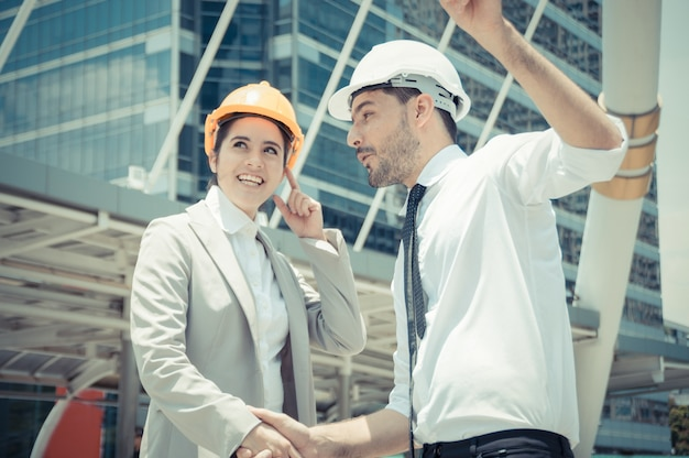 Professional engineers, young men and young women are planning construction.