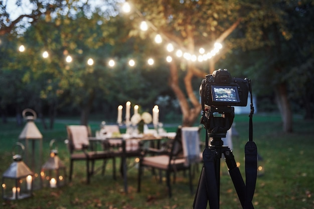 Professional equipment. camera on the tripod stand in the field in front of prepared table at evening time