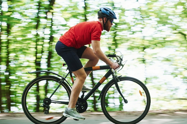 Professional equipment. cyclist on a bike is on the asphalt road in the forest at sunny day