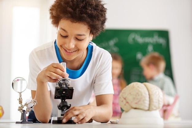 전문 장비. 생물학 실험실에있는 동안 현미경을 사용하여 기쁘게 좋은 소년