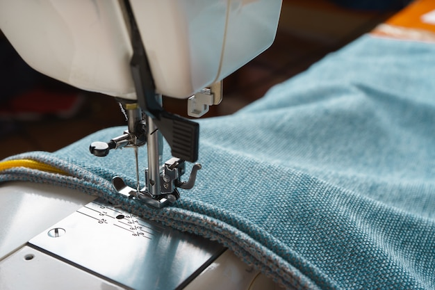 Professional equipment. modern sewing machine with special pressure foot. the process of sewing a decorative edging cord of blue item of clothing.