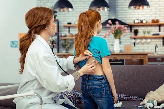 전문 장비. 그녀의 환자의 건강을 확인하는 동안 청진기를 사용하는 전문 여성 의사
