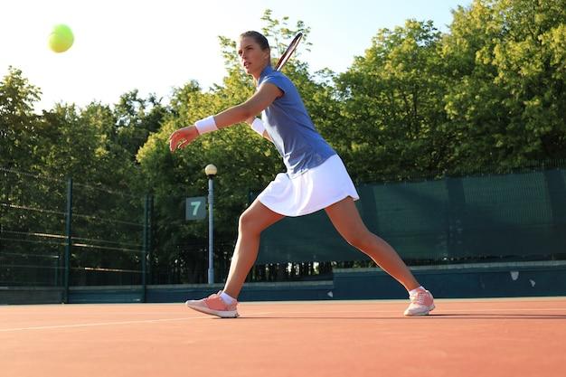 ラケットでテニスボールを激しく叩くプロ装備の女子テニス選手。