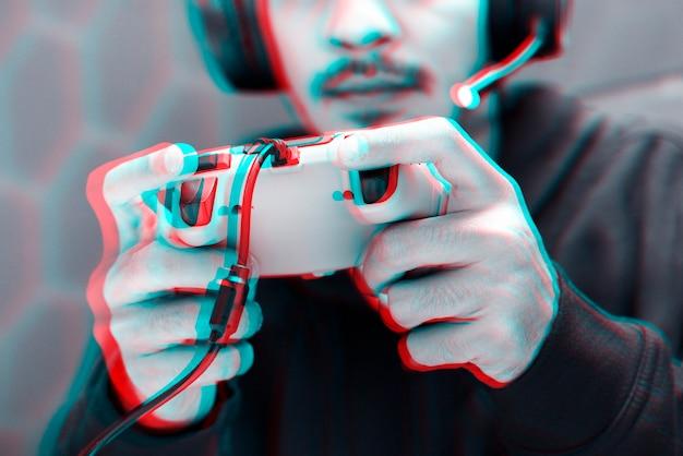 Профессиональный киберспортсмен играет в игру с игровым контроллером с эффектом двойной цветовой экспозиции