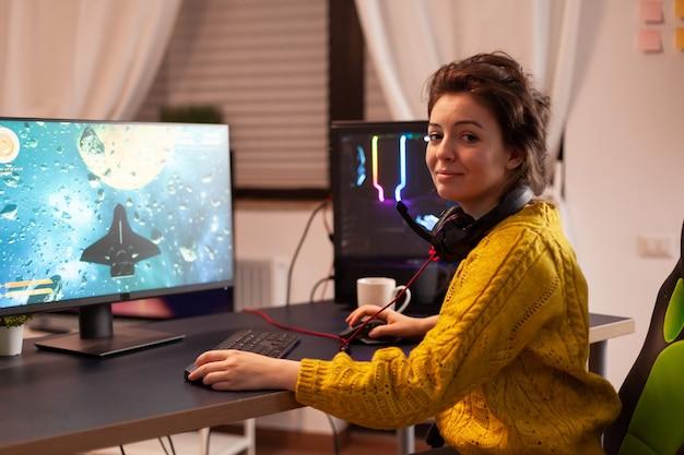 챔피언십 이벤트에서 비디오 게임을 하는 동안 카메라를 보며 웃고 있는 전문 e스포츠 여성 게이머. 게임 토너먼트 동안 강력한 개인용 컴퓨터에서 수행하는 온라인 스트리밍 사이버.