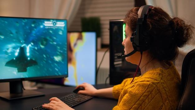 ヘッドセットのマイクを使用して、ストリーミングサービスでチームとシューティングゲームをプレイしているプロのeスポーツ女性ゲーマー。サイバースペースでの仮想シューティングゲーム、pcゲームトーナメントでパフォーマンスするeスポーツプレーヤー