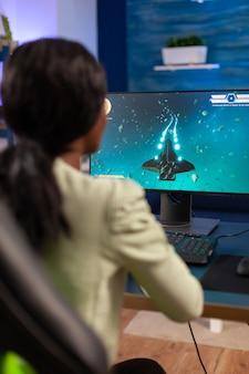 Профессиональный игрок в киберспорт во время онлайн-чемпионата с джойстиком. соревновательная женщина-кибер-игрок, выполняющая турнир по видеоиграм, использует профессиональный джойстик.