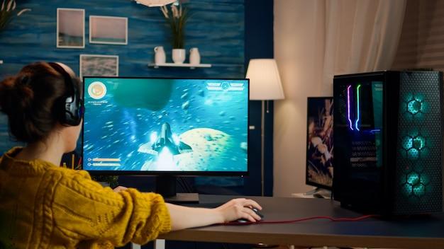 新しいグラフィックとたくさんのアクションを備えたシューターモックアップビデオゲームをプレイするプロのeスポーツゲーマー。現代のstを使用して、強力なrgbコンピューターでゲームトーナメントをプレイするプロeスポーツチームプレーヤーストリーマー