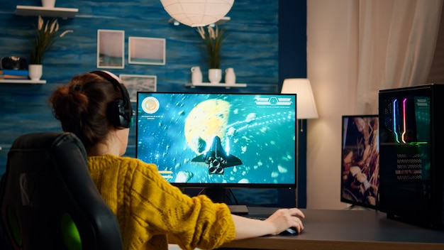 전문 e스포츠 게이머는 헤드셋을 사용하여 컴퓨터에서 슈퍼 액션과 특수 효과가 있는 3d 슈터 모형 비디오 게임을 능숙하게 플레이합니다. 세련된 방에서 강력한 pc로 사이버 수행