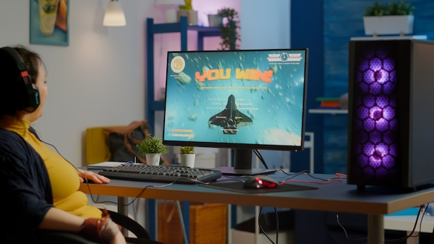 Giocatrice professionista di esports che gioca su un potente videogioco per computer rgb, celebrando la vittoria. pro cyber streaming alzando la mano vincendo torneo, campionato online di esport da studio di gioco