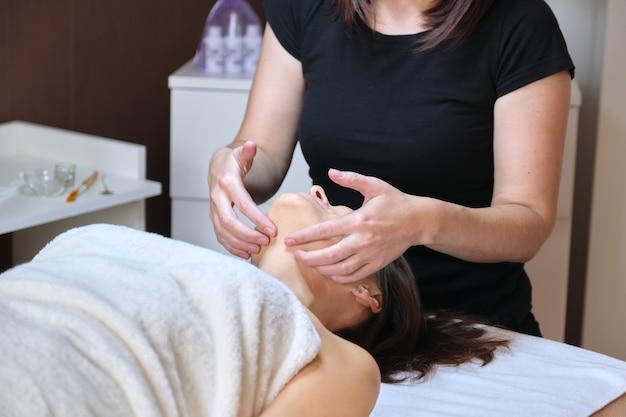 Профессиональный массаж лица, спа, красота, концепция лица. женщина средних лет получает антивозрастной массаж, лечение в клинике